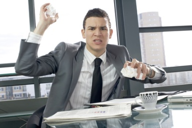 Image of man throwing crumpled paper in an office