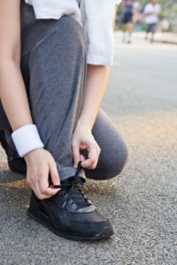 Image of a woman tying her shoe.